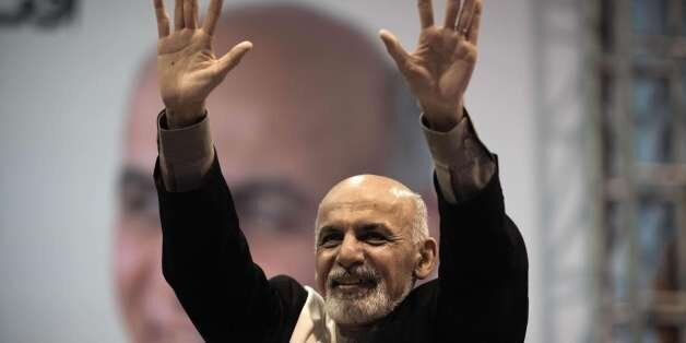 Afghan presidential candidate Ashraf Ghani gestures towards a crowd in an assembly hall in Kabul on Februray 13, 2014. Ghani