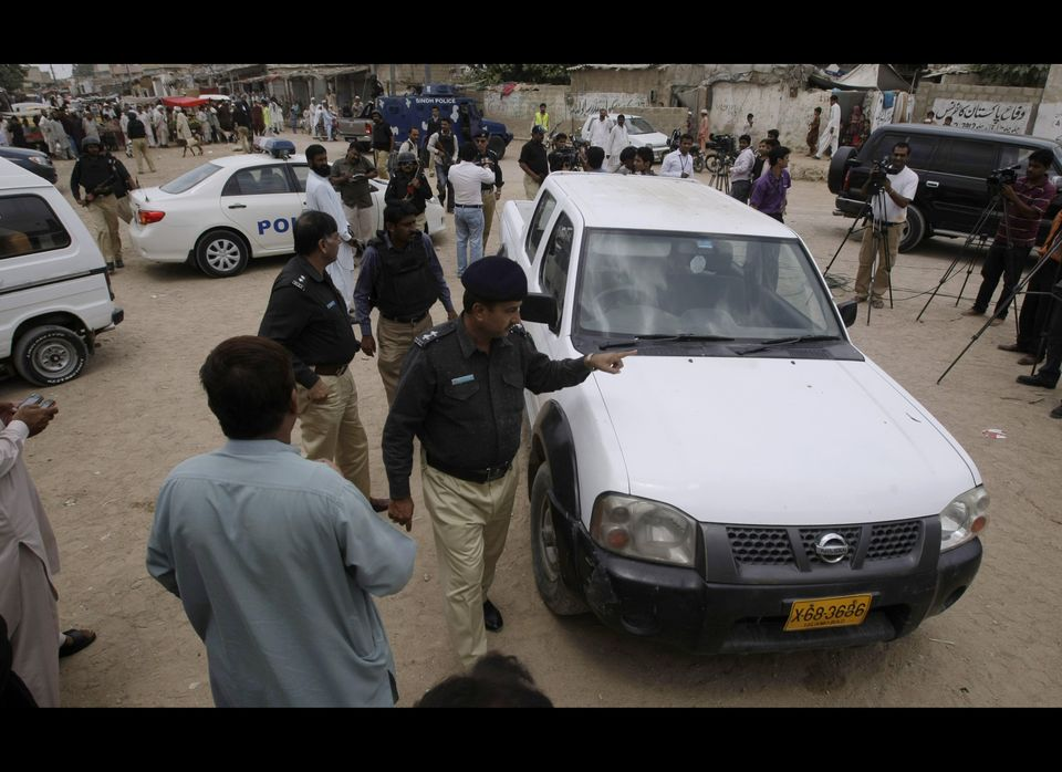 Pakistani police officers gather by a vehicle which was attacked by gunmen in Karachi, Pakistan, Tuesday, July 17, 2012. (AP