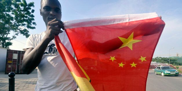 A man poses with Congo and China flags on March 28, 2013 , in Brazzaville on the eve of the visit from China's new President