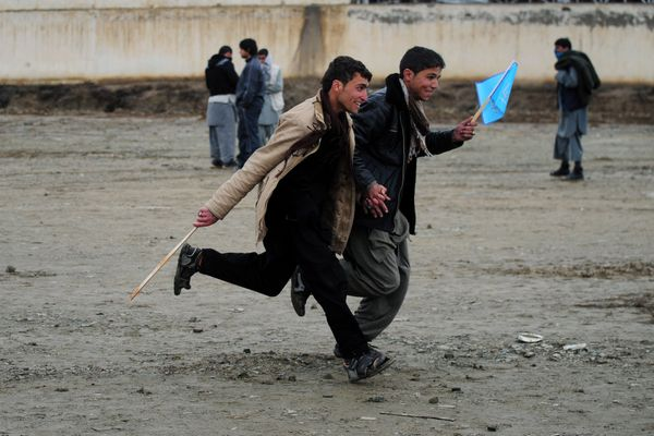 Afghan supporters run to get a good spot near the stage to see Afghan presidential candidate Abudullah Abdullah speak at an e