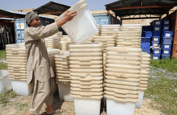 An Afghan election worker prepares to load plastic boxes containing election material onto a truck at a warehouse for polling
