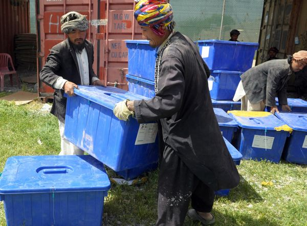 Afghan election workers load plastic boxes containing election material onto a truck at a warehouse for polling stations in K