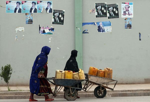 Afghan women push wheelbarrows filled with jerry cans past electoral posters on a street in Kandahar on April 1, 2014. (BANAR