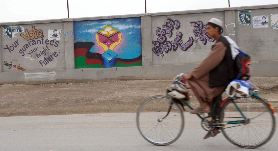 An Afghan cyclist rides past a wall with an election-themed mural and slogan in Kandahar on April 1, 2014. (BANARAS KHAN/AFP/