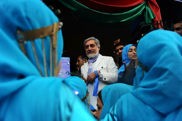 Afghan presidential candidate Abdullah Abdullah speaks with schoolgirls during a campaign rally at a stadium in the northwest