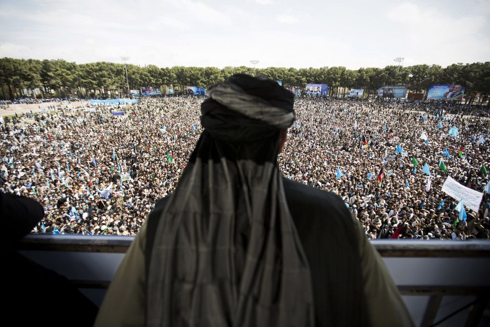 An Afghan man watches the crowd supporting presidential candidate Abdullah Abdullah during a campaign rally at a stadium in t