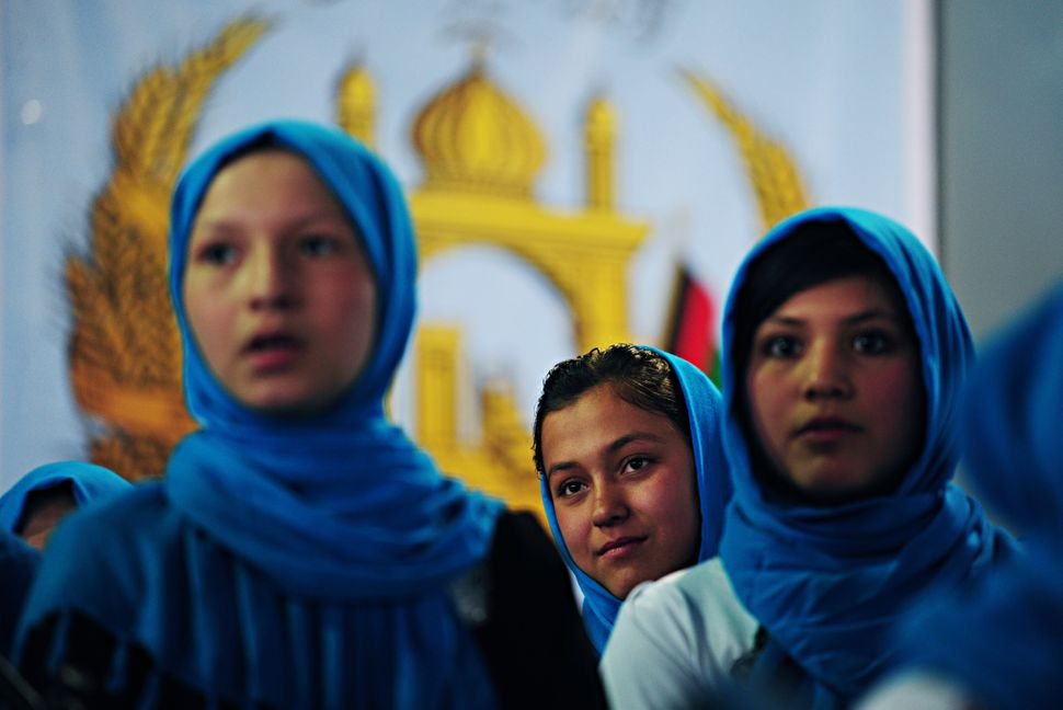 Afghan schoolgirls stand onstage in front of their country's coat-of-arms as they prepare to sing the national anthem during