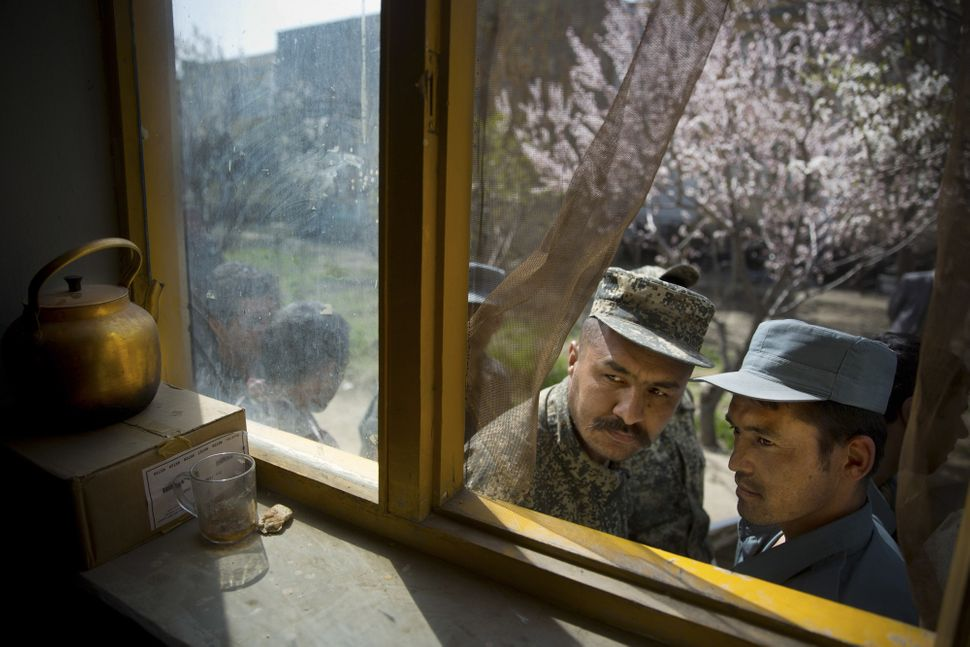 An Afghan soldier (left) and a policeman peek through a window as they queue with others to get their registration card, on t