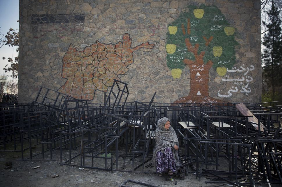 An Afghan woman sits on destroyed school benches as she waits to get her registration card on the last day of voter registrat