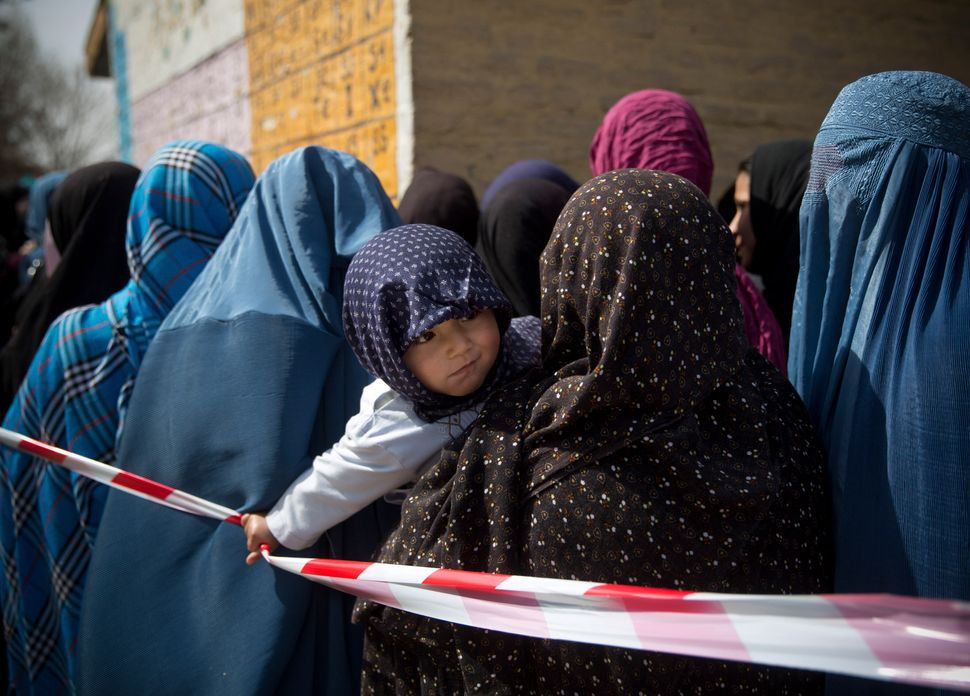 A child pulls a rope which keeps Afghan women in line queuing to get their registration card, on the last day of voter regist