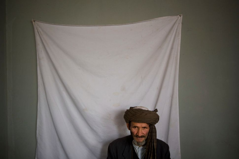 An Afghan man waits to have his picture taken for his registration card, on the last day of voter registration for the upcomi