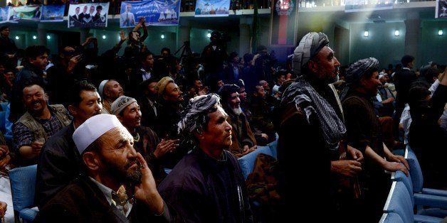 A ray of late afternoon light shines on Afghan men listening to a presidential candidate during a speech at a local hall on A