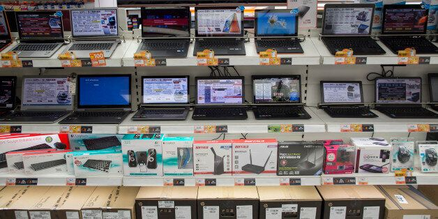 Lenovo Group Ltd. laptop computers are displayed on shelves above routers, keyboards and speakers in a Fortress electronics s