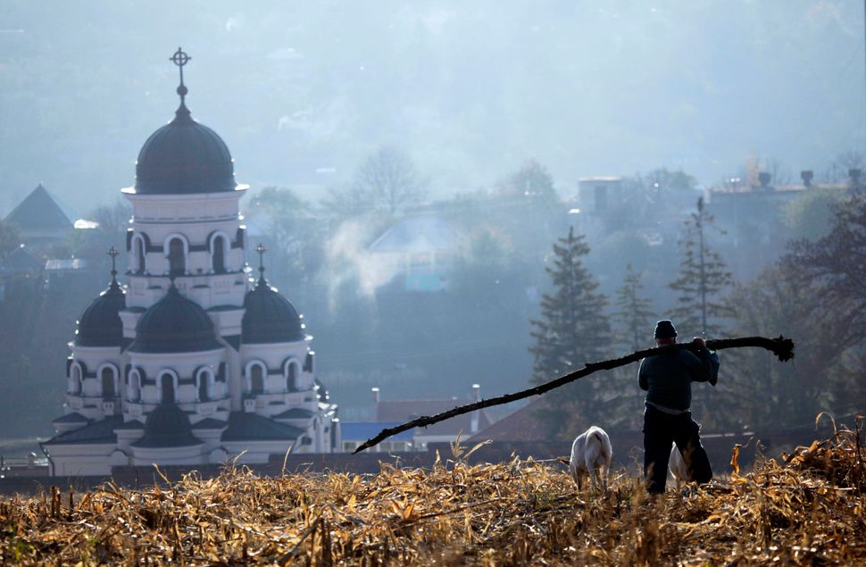 A Moldovan farm worker carries the trunk of a fallen tree through the corn fields in front of the Capriana monastery in Capri