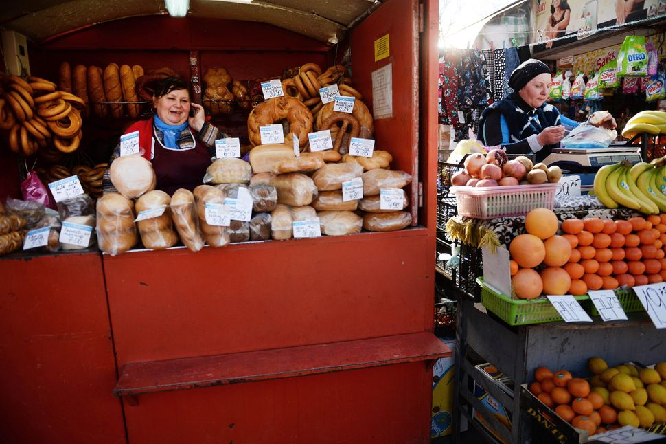 Zenovia (L), 58, a bread seller, is pictured next to a woman who sells fruits at the central market in Chisinau, Moldova, on