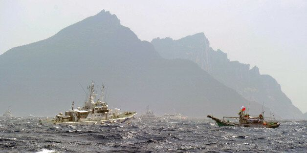 A Taiwan fishing boat (R) is blocked by a Japan Coast Guard (L) vessel near the disputed Diaoyu / Senkaku islands in the East
