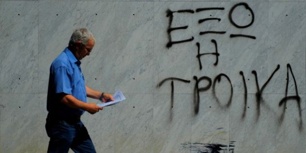 A man holds papers as he passes outside of a branch of Bank of Cyprus with a painting that reading in