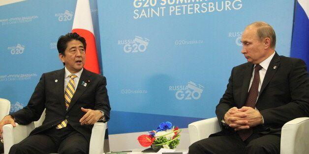 SAINT PETERSBURG - SEPTEMBER 05:  Russian President Vladimir Putin (R) greets Japanese Prime Minister Shinzo Abe (L)  at the