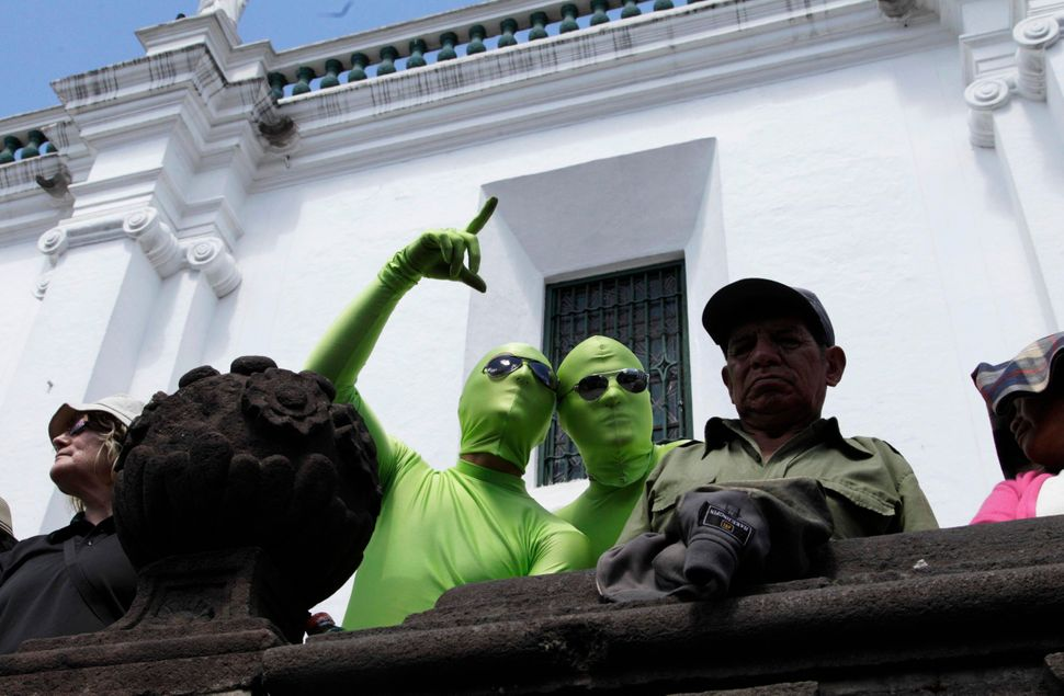 Two men dressed as limes, promoting an energy drink, stop to watch the weekly changing of the guard ceremony in Quito, Ecuado