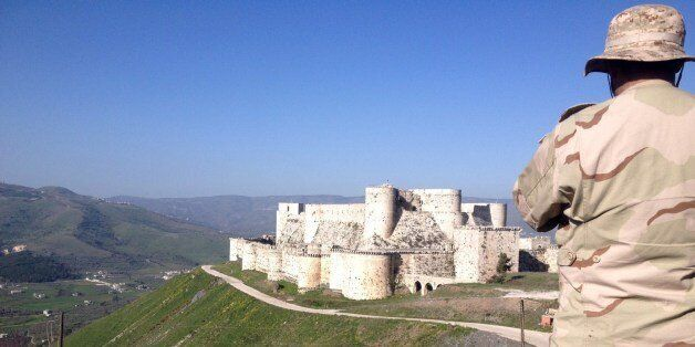 A government soldier looks out over the renowned Crusader castle Krak des Chevaliers near the Syria-Lebanon border after forc
