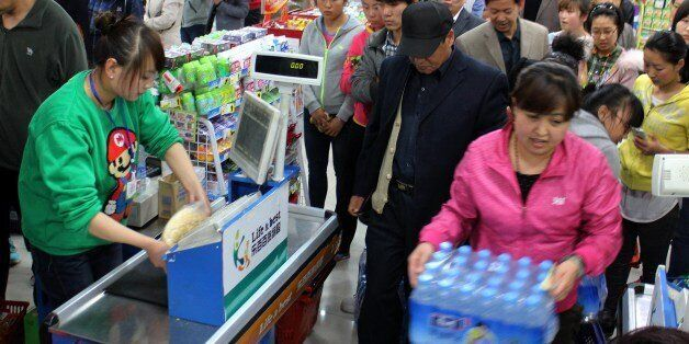 This picture taken on April 11, 2014 shows people buying bottled water in a supermarket in Lanzhou, northwest China's Gansu p