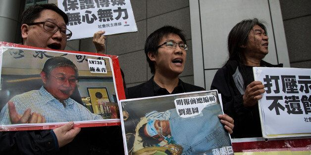 HONG KONG - FEBRUARY 27:  Pro-democracy activists hold a sign with an image of former chief editor of the Ming Pao daily Kevi