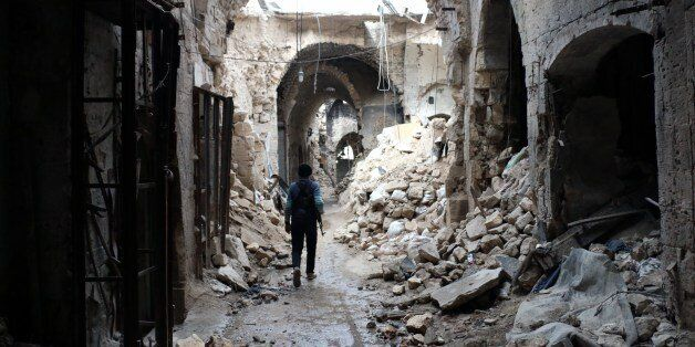 A rebel fighter walks in a devastated alley of Aleppo's old market, in the UNESCO-listed northern Syrian city on February 27,
