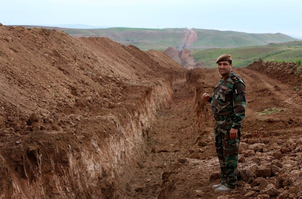 A member of the Iraqi security forces looks on during the digging operations to build a trench on the northern Iraqi border w