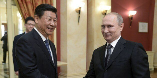 Russia's President Vladimir Putin (R) shakes hands with his Chinese counterpart Xi Jinping before a reception to greet high-r