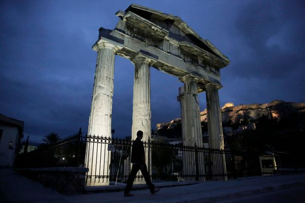 A man walks in front of the gate of the ancient Roman Agora, with the Acropolis in the background, in Athens, Feb. 5, 2014. (