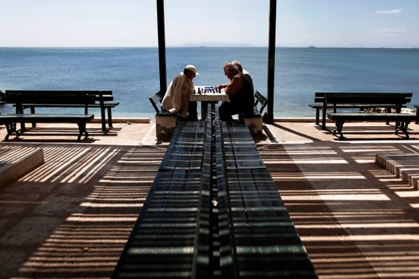 Greek men play chess in the Faliro Coastal Zone near Athens, April 18, 2013. (Petros Giannakouris/AP)