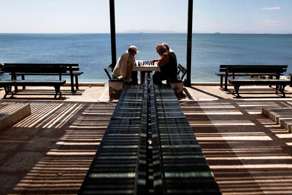 Greek men play chess in the Faliro Coastal Zone near Athens, April 18, 2013. (Petros Giannakouris/AP)
