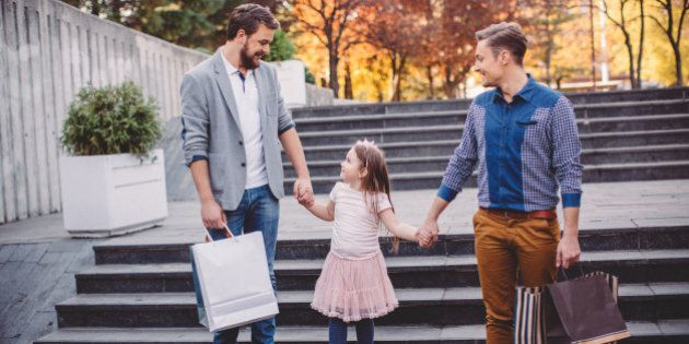 Young gay parents with their daughter walking from the shopping mall. They are happy and joyful. Caucasian...