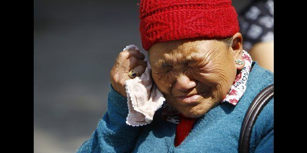 Mother of Nepalese mountaineer Ang Kaji Sherpa, killed in an avalanche on Mount Everest, cries while she waits for his body a