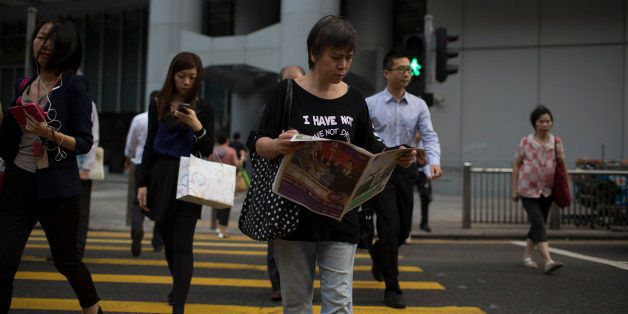 A woman reads a newspaper as she crosses a street in the business district of Central in Hong Kong, China, on Tuesday, Oct. 1