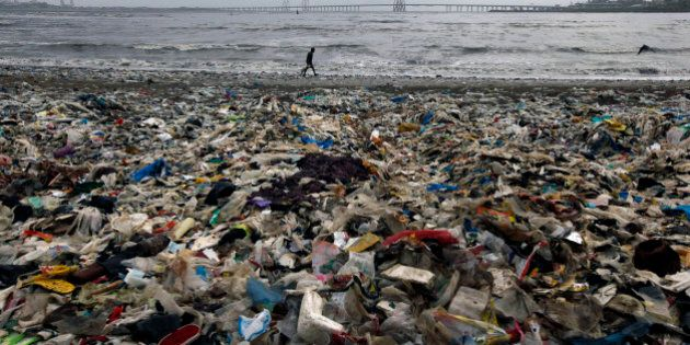 A man walks by the Arabian Sea coast piled with garbage, mostly plastic waste, in Mumbai, India, Monday,...