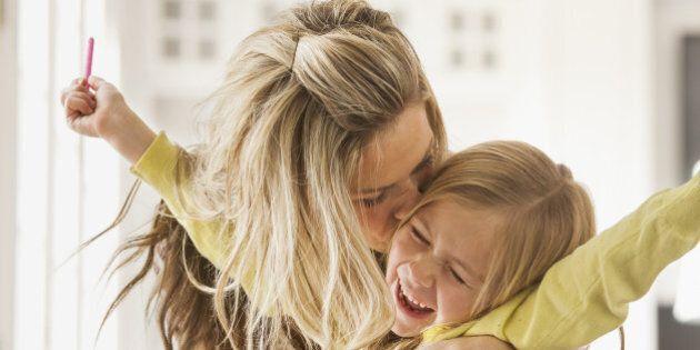 USA, Utah, Lehi, Mother kissing daughter (6-7) during doing