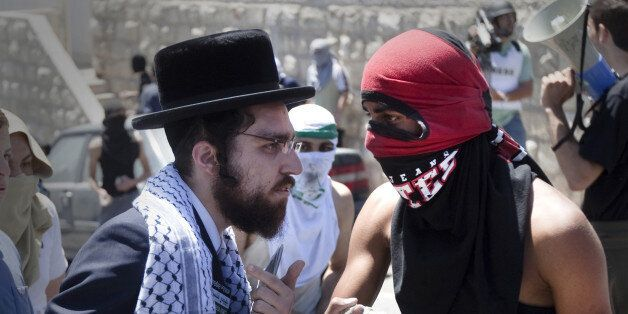 A member of Neturei Karta, a fringe of ultra-Orthodox movement within the anti-Zionist bloc in Israel, talks with a masked Pa
