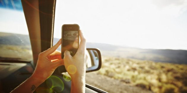 Woman riding in front seat of car driving through desert taking digital photo with