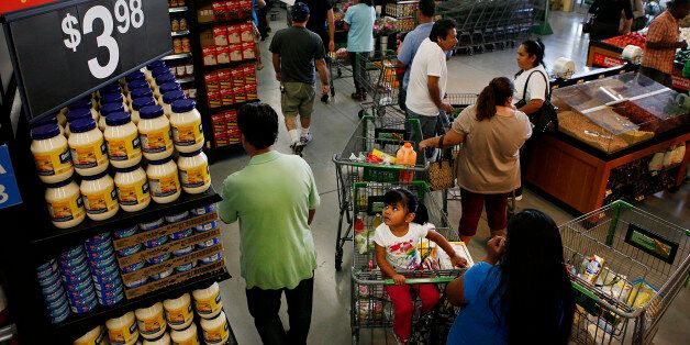 Customers wait in line to check out during the grand opening of a Wal-Mart Stores Inc. location in Panorama City, California,