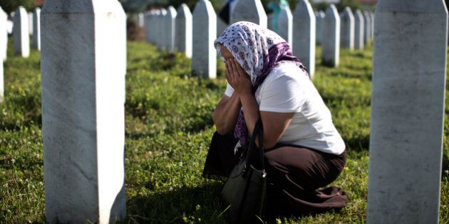 A woman cries as she visits the grave of a family member at the Potocari memorial complex near Srebrenica,...