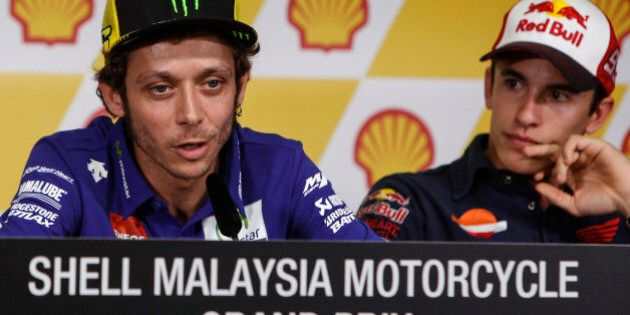 MotoGP rider Valentino Rossi of Italy, left, speaks while Marc Marquez of Spain looks on during a press...