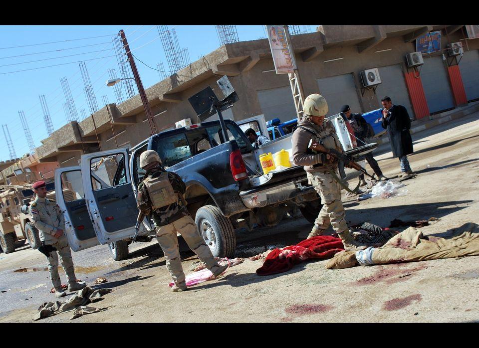 Iraqi police look at the bodies of slain policemen in the western city of Haditha on March 5, 2012. Suspected Al-Qaeda gunmen