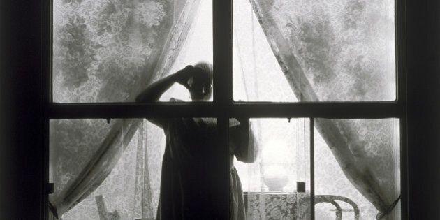 A woman standing behind a livingroom