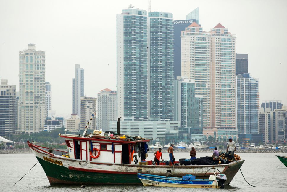 Fishermen rest on their boat with skyline of Panama City, Wednesday, April 30, 2014.  (Arnulfo Franco/AP)