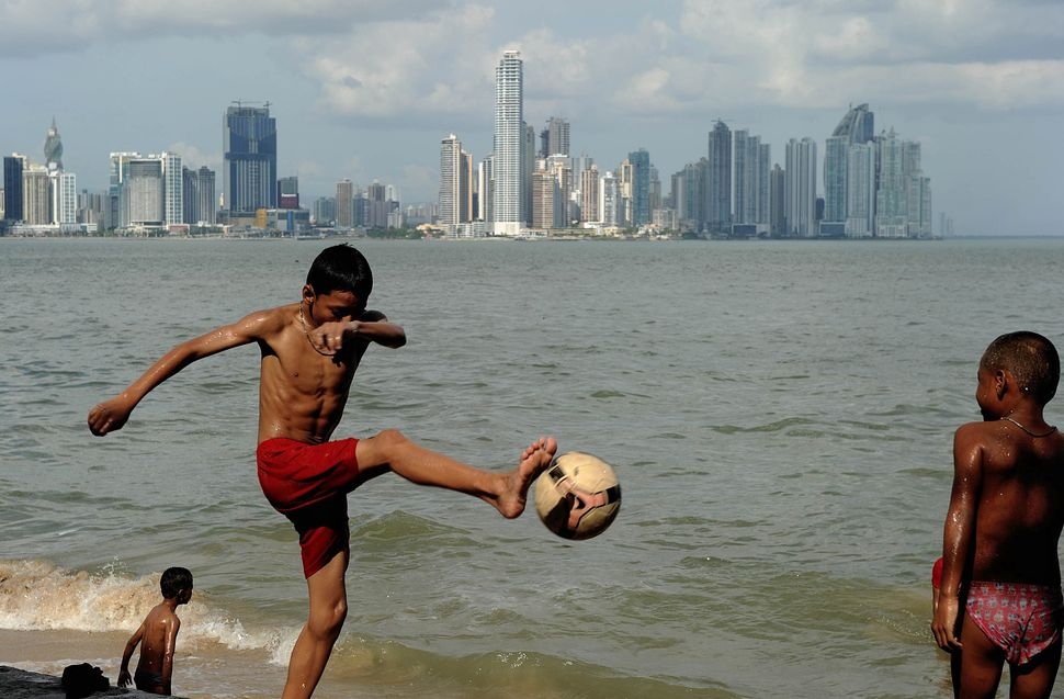 A Panamanian boy kicks a football near the water in the Panama Bay with the Panama City skyline in the back on January 19, 20