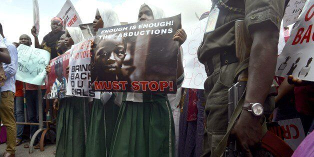 A policeman stand beside children holding as members of Lagos based civil society groups hold rally calling for the release o