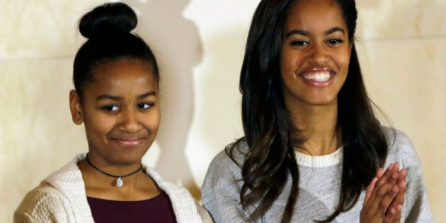 U.S. President Barack Obama's daughters Sasha (L) and Malia listen to their father during the pardoning...