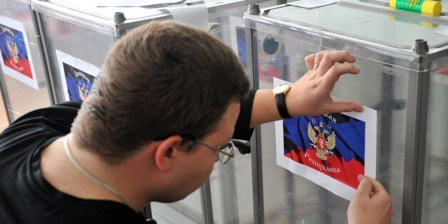 A member of the regional election commission glues a sticker depicting the flag of the self-proclaimed  Donetsk People's Repu