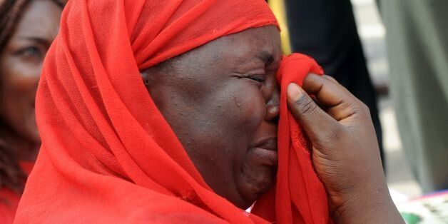 One of the mothers of the missing Chibok school girls wipes her tears as she cries during a rally by civil society groups pre
